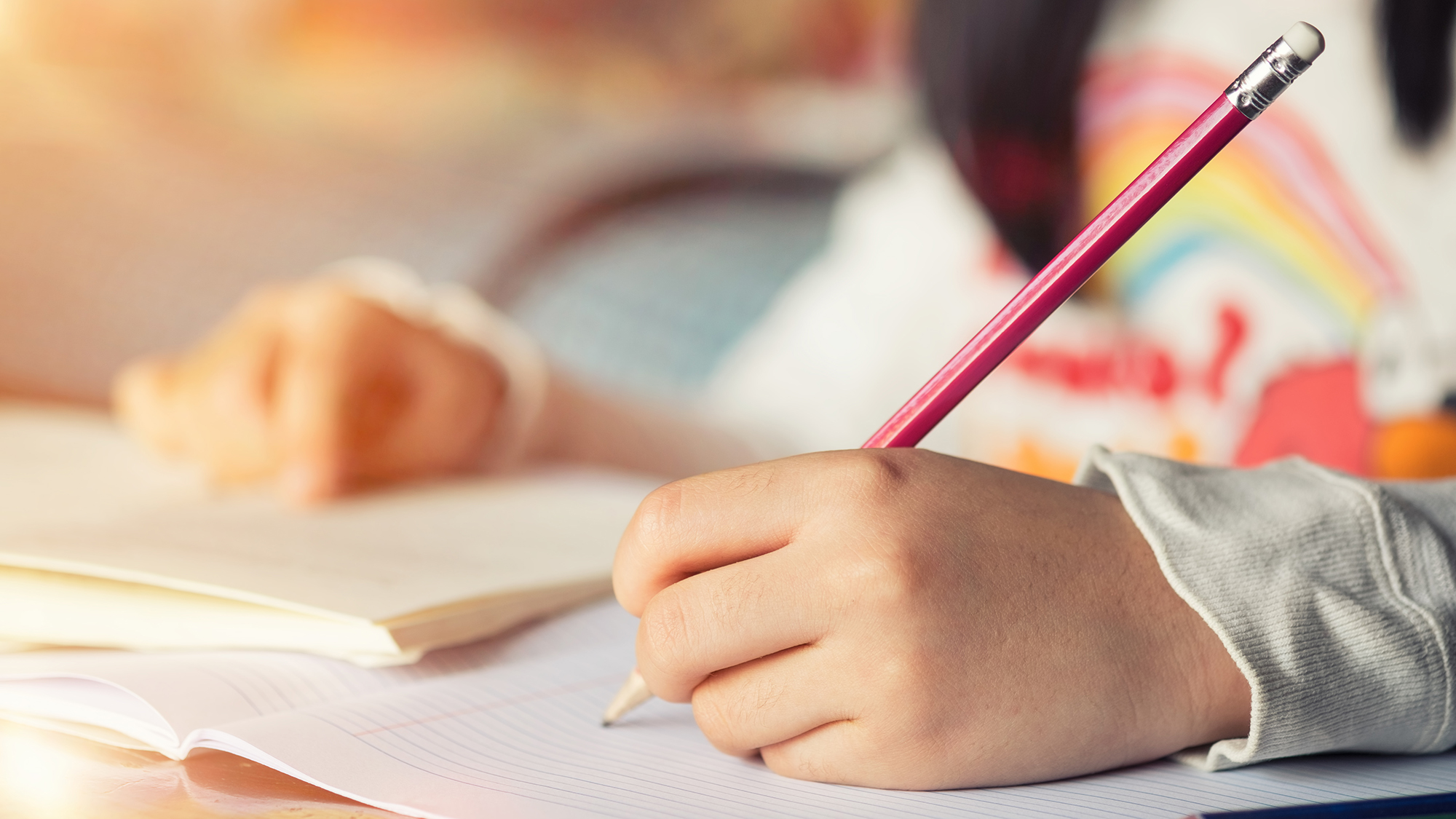 Girl sits at desk doing homework, hand writing in notebook